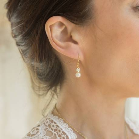 white pearl drop earrings with gold hearts on fish hooks being worn