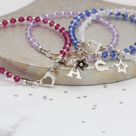 Crystal friendship stack bracelets in pink, white, mauve and blue, add a silver charm for a perfect personalised gift