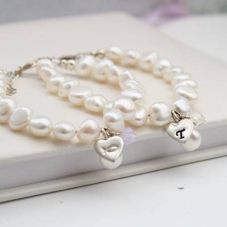 beloved childs white pearl christening bracelet personalised with her initial on a silver charm